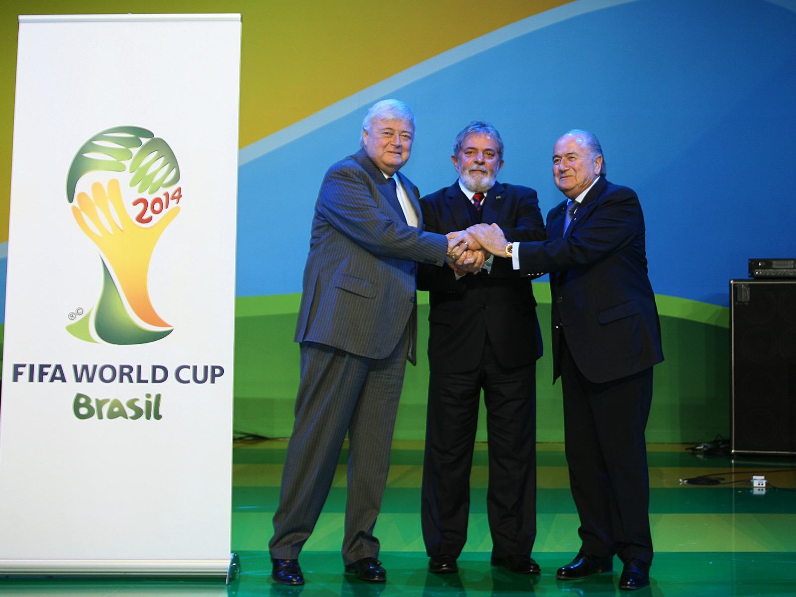 Le président Lula (au centre) et le président de la FIFA Seppe Blatter (à gauche) lors de la présidentation du logo du Mondial 2014 (Crédit photo : Ricardo Stuckert, Wikimedia Commons)